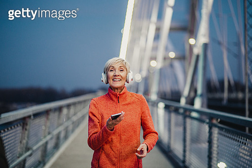 Senior woman is outdoors jogging holding smart phone and with headphones - gettyimageskorea