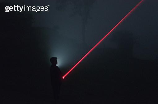 Silhouette Man Standing On Illuminated Road At Night - gettyimageskorea
