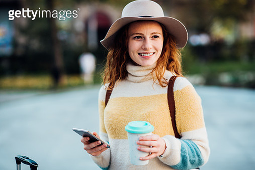 Portrait of a beautiful, young female tourist drinking coffee and using a smartphone. - gettyimageskorea