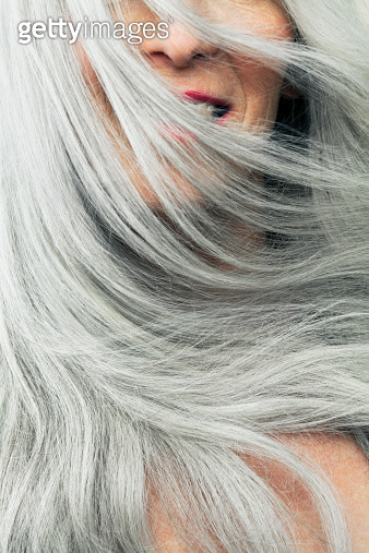 Mature woman with wind blown gray hair, cropped. - gettyimageskorea