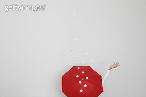 Conceptual woman standing in snow holding an open umbrella - gettyimageskorea