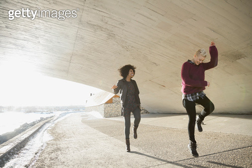 Female friends dancing under city bridge - gettyimageskorea