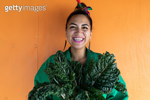 Woman smiling holding silverbeet leaves looking at camera - gettyimageskorea