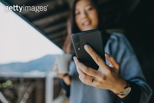 Young Asian woman using smartphone while relaxing with coffee in the balcony on a fresh morning - gettyimageskorea