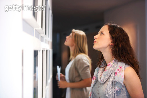 Two female friends viewing paintings while attending an exhibition - gettyimageskorea