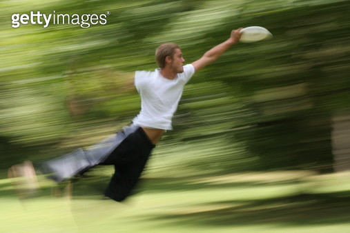 Jumping to Catch a Frisbee - gettyimageskorea
