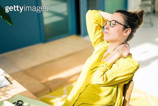 Young fashion designer relaxing at desk in her studio - gettyimageskorea