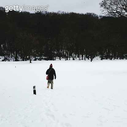 Rear View Of Man On Snow Field - gettyimageskorea
