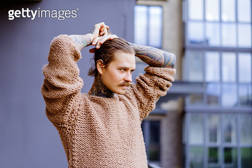 Handsome tattooed sexy man with long hair and mustache outdoors - gettyimageskorea
