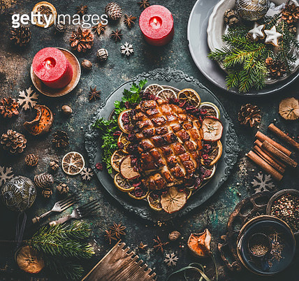 Christmas dinner table with roasted pork ham served on vintage plate with winter flavors, table place setting with festive holiday decoration, fir branches , cutlery and candles on dark rustic background, top view - gettyimageskorea