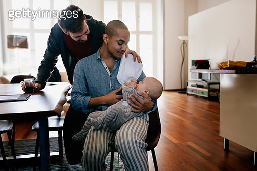 Black gay father and partner feeding baby bottle - gettyimageskorea