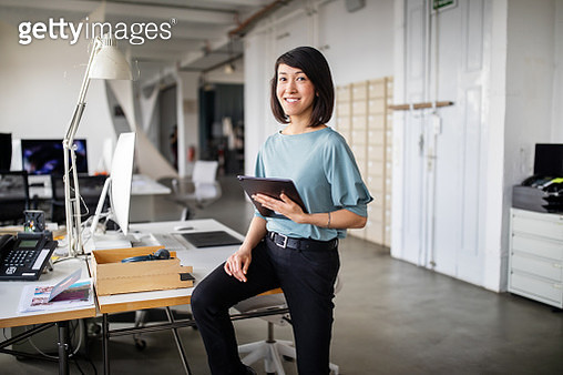 Confident female business professional with digital tablet - gettyimageskorea