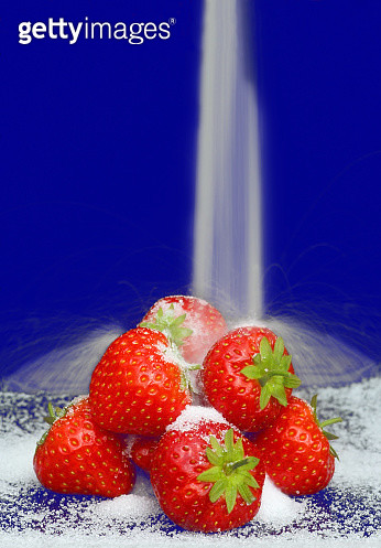 Ripe strawberries with sugar falling onto them on blue - gettyimageskorea
