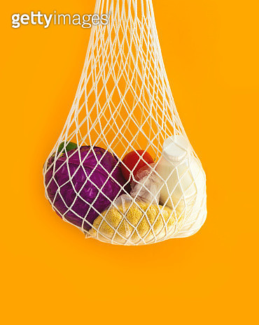 The mesh eco-shopping bag with with cereals, milk and vegetables on a yellow background. The modern reusable purchasing, the concept of zero waste. - gettyimageskorea