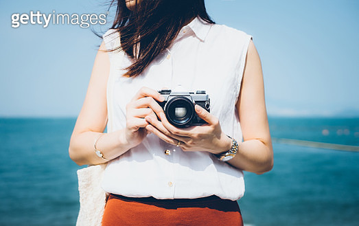 Girl taking photos with vintage film camera in the beach on a sunny day - gettyimageskorea