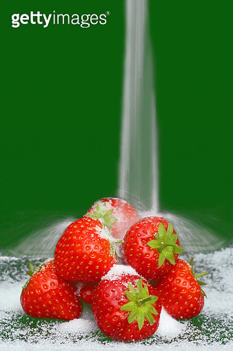 Ripe strawberries with sugar falling onto them on green - gettyimageskorea