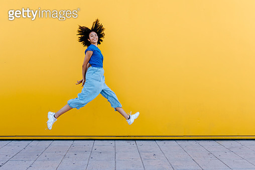 Pretty woman jumping for joy in front of yellow wall - gettyimageskorea
