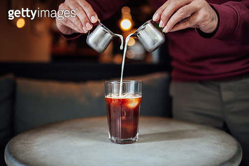 Man pouring milk in iced coffee - gettyimageskorea