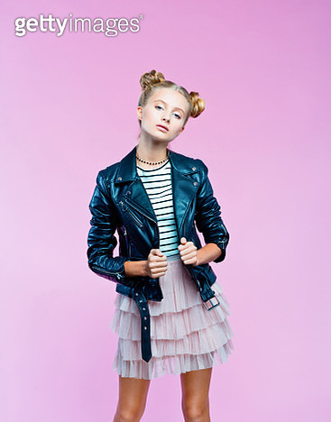 Female teenager wearing black leather jacket, pink tulle skirt and striped top looking at camera. Studio shot on pink background. - gettyimageskorea