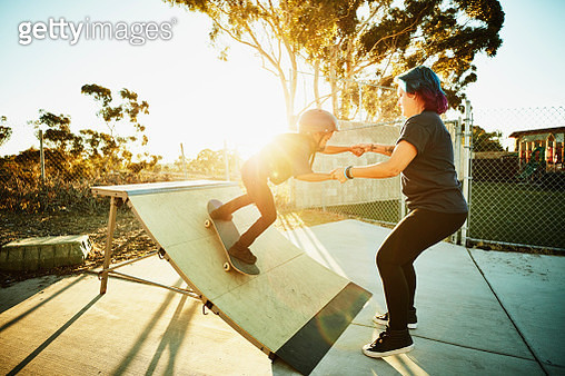 Female skateboard instructor helping young female student ride ramp during skate camp - gettyimageskorea