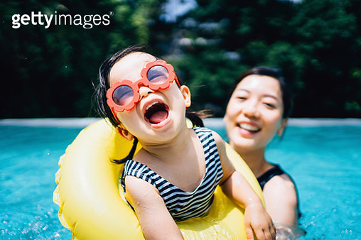 Happy Asian toddler girl with sunglasses smiling joyfully and enjoying family bonding time with mother having fun in the swimming pool in summer - gettyimageskorea