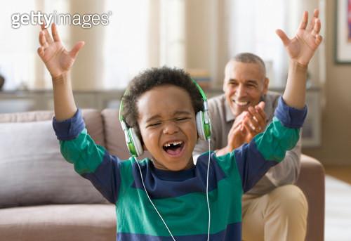 Grandfather watching grandson listening to music on headphones - gettyimageskorea