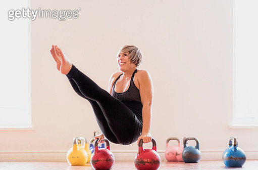 Mature woman balancing between two kettlebells - gettyimageskorea