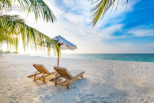 Vacation in tropical countries. Beach chairs, umbrella and palms on the beach. - gettyimageskorea