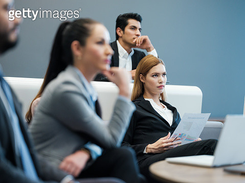 A young businesswoman sitting in a meeting with her colleagues as she listens carefully. - gettyimageskorea