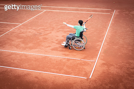 Teenage boy in wheelchair playing tennis - gettyimageskorea
