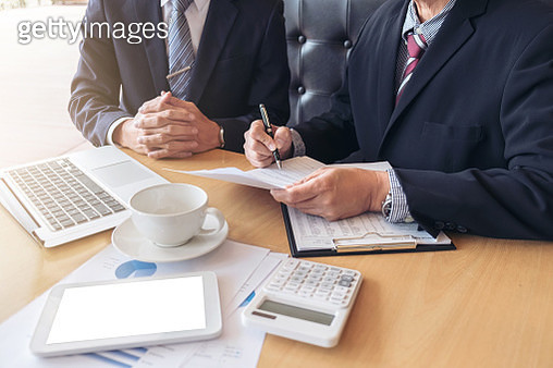 Midsection Of Businessmen Discussing Over Graph At Desk - gettyimageskorea