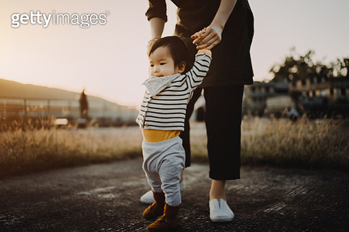Mother holding baby daughter's hand helping her learn to walk in the park during sunset - gettyimageskorea