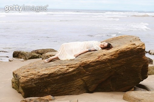 Woman Lying Down On Rock At Beach - gettyimageskorea