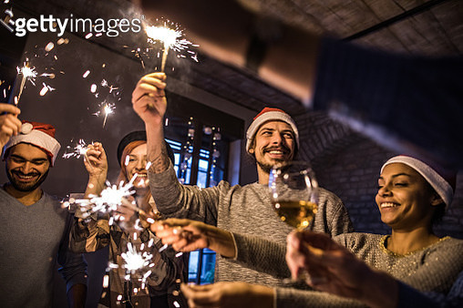 Group of happy friends having fun while celebrating New Year with sparklers in the office. - gettyimageskorea