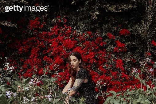 Young Woman With Eyes Closed Sitting Amidst Plants In Park - gettyimageskorea