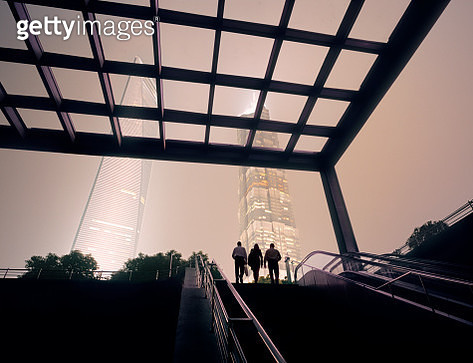 Businessmen and businesswoman on top of stairs at modern business district - gettyimageskorea