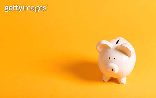 White piggy bank on yellow - gettyimageskorea