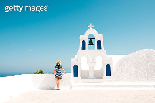Greece, Santorini, Oia, back view of woman standing next to bell tower looking to the sea - gettyimageskorea