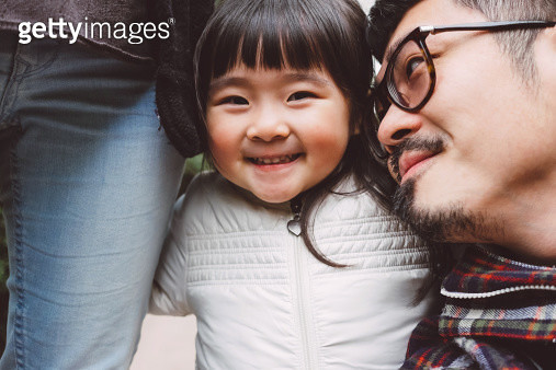 Lovely little girl looking at the camera joyfully with one arm hugging mom's leg & another arm hugging dad's shoulder. - gettyimageskorea