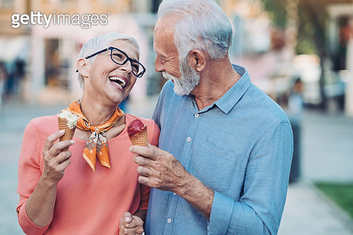 Senior couple holding ice cream cones outdoors the city - gettyimageskorea