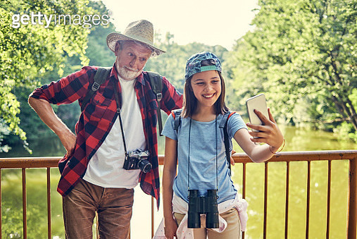 cheerful granddaughter taking a selfie with her grandfather while hiking - gettyimageskorea