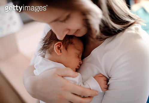 A young woman cuddling her new baby boy or girl with love. - gettyimageskorea