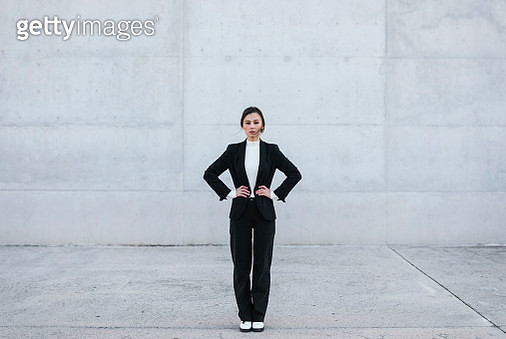 Young woman wearing black suit standing in front of concrete wall - gettyimageskorea