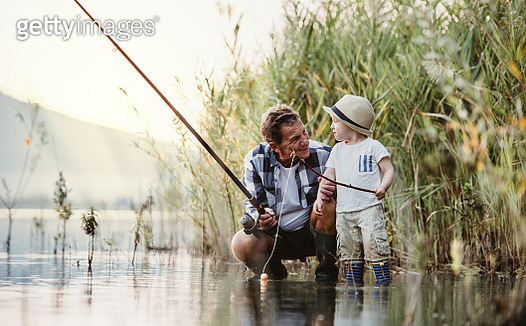A senior man with a toddler boy fishing together on a lake. - gettyimageskorea