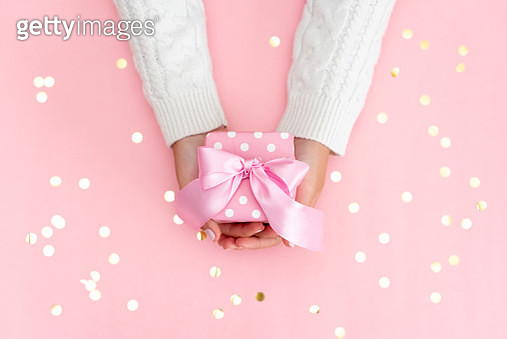 Woman's hands with manicure hold gift box with brown ribbon on pale pink background. Festive concept. Place for text - gettyimageskorea
