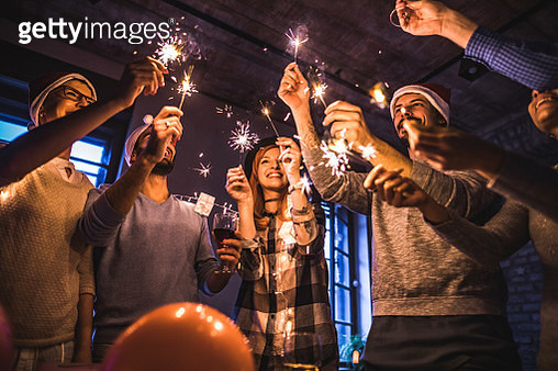 Below view of happy colleagues using sparklers while celebrating New Year in the office. - gettyimageskorea