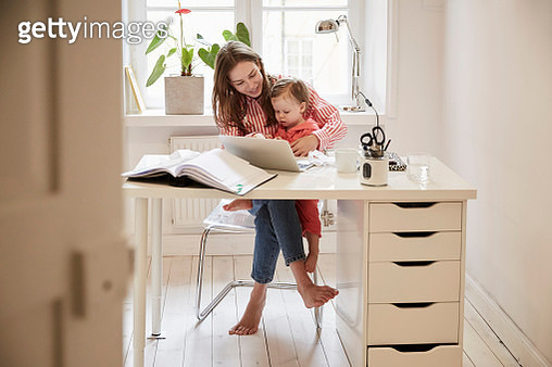 Female accountant sitting with daughter while working on laptop at home - gettyimageskorea