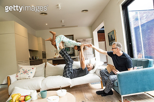 Dads and daughter playing on couch - gettyimageskorea