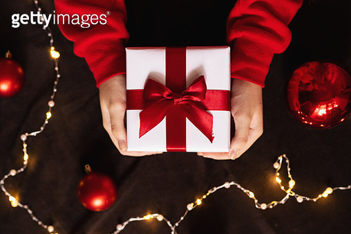 Christmas gift with red ribbon in hand on red background. Lights and Christmas balls. - gettyimageskorea