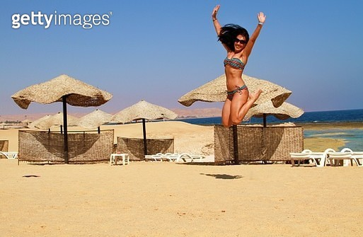 Full Length Of Woman Jumping At Beach Against Sky - gettyimageskorea